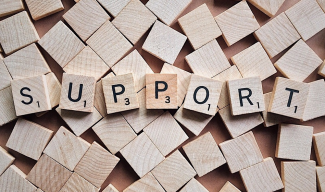 "Scrabble letters spelling the word ""support"""
